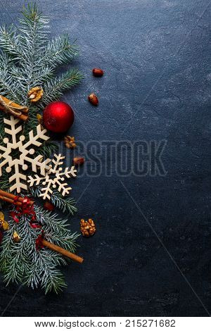 On a dark background, the Christmas tree is decorated with wooden snowflakes, Christmas balls and cinnamon sticks. Place for the inscription. View from above. Indoors.