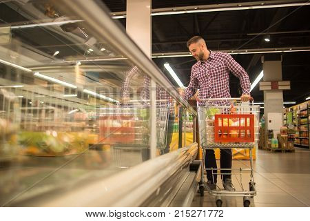Full length portrait of handsome young man with shopping cart choosing groceries in supermarket looking at frozen foods in freezer