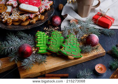 On a wooden board are three Christmas gingerbreads in the shape of a Christmas tree with a green sweet glaze, alongside decorative twigs of a Christmas tree.