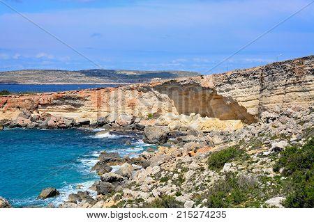 Rocky coastline with Comino to the rear Paradise Bay Malta Europe.