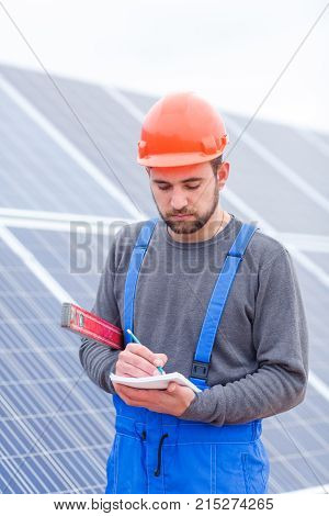 A solar station worker in blue uniform and in an orange helmet, holds a waterpas in his hands and writes something into a notepad.