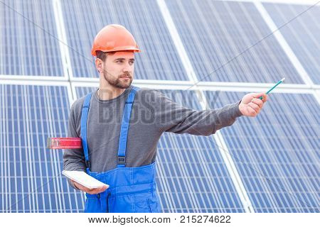 A young worker stands a solar cell station in uniform and a helmet holds a waterpas and a notebook in his hands and shows a hand somewhere. Outdoors.