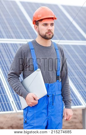 An employee of the solar battery station with a beard, dressed in uniform and a helmet stands and looks somewhere with a serious look, holding a gray modern laptop in his hands. Outdoors.