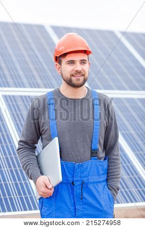 Stations of solar battery. The worker in blue uniform and in an orange helmet stands near the panel and holds a modern laptop in his hands and looks somewhere far away. Outdoors.