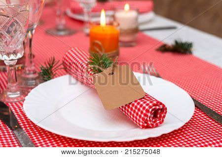 Festive composition with candles and plates. Table decoration. A beautiful table setting red table cloth tablecloth in the box. Christmas dinner. A Napkin decorated with inscription Merry Christmas.