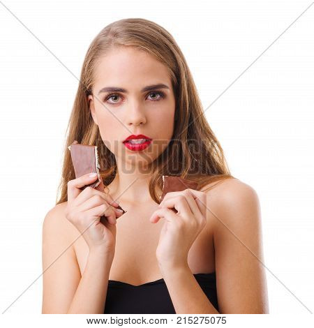 A young attractive girl is holding a delicious and sweet milk chocolate in her hands. Isolated on white background. Indoors.