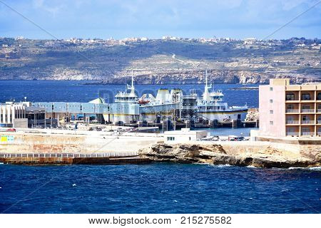 PARADISE BAY, MALTA, APRIL 2, 2017 - Gozo ferry in the ferry terminal with Gozo and Comino to the rear Paradise Bay Malta Europe, April 2, 2017.