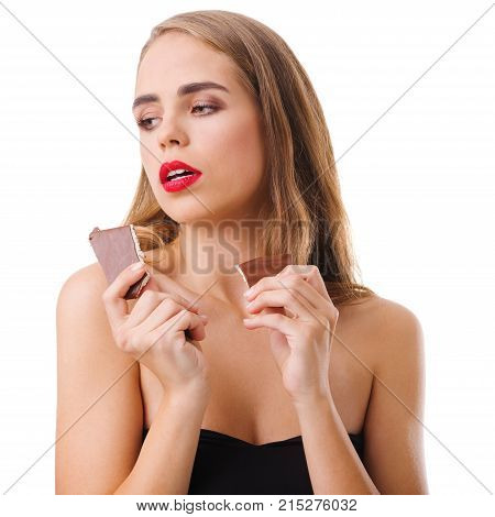 A cute young brunette girl with long hair and red lips holds a piece of milk chocolate in her hands and looks to the side. Isolated on white background. Indoors.