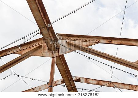 Open overhead girders and trusses covered in rust horizontal aspect