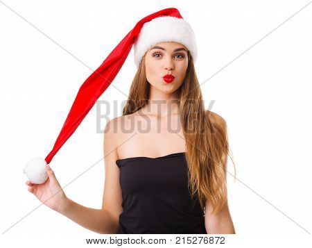 Beautiful girl squeezed her red lips and holds on to the pompon Christmas red hat. Isolated on white background.
