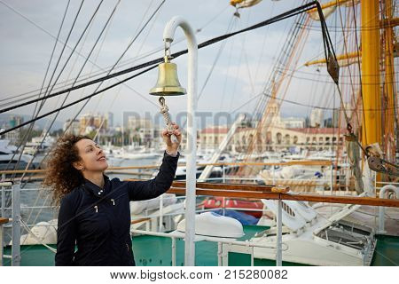 Woman with curly hair in dark jacket clangs bell on ship deck.