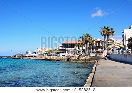 MELLIEHA, MALTA - APRIL 2, 2017 - Pavement cafes in the harbour with boats in dry dock to the rear Mellieha Malta Europe, April 2, 2017.