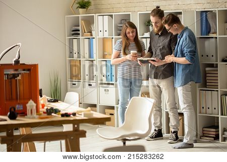 Handsome bearded designer showing results of accomplished work to his colleagues while having informal meeting at open plan office, 3D printer and small prototypes located on desk