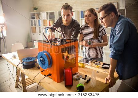 Three young engineers standing at wooden desk and using 3D printer in order make small prototypes, interior of modern laboratory on background
