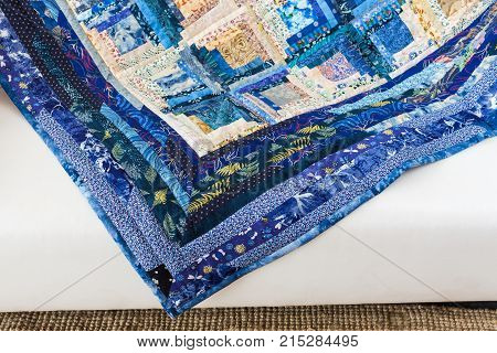 patchwork, culture, design, applique, creativity, sewing concept - there are flowers, leaves, dots, plants and insects on the print of blue colored quilt made in american technique - piecework