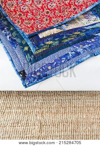 decoration, color design, texture, garment manufacturing, sewing concept - there is combination of bright red and calm blue colores in folksy blanket made of satin rags in traditional style