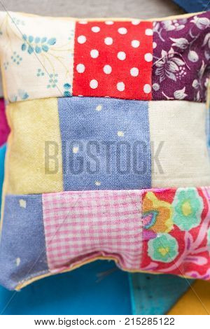 patchwork, quilting, sewing, tailoring and fashion concept - close-up on beautiful colorful stitched pincushion without pins, macro on background of bright flaps of fabric, flat lay, top view