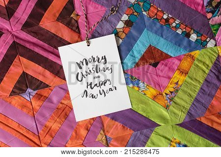 christmas, sewing, present concept. squares of textile patches of different colores and patterns sewed in one bright blanket and there is small greeting card on it