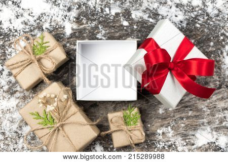 Open And Blank White Gift With Red Ribbon Bow On Wooden Background With Wrapped Brown Craft Handmade