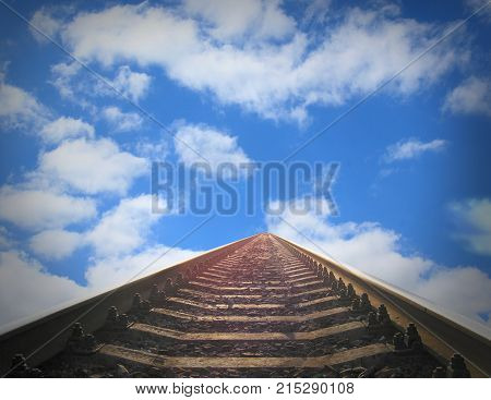 landscape with rails going away into the blue cloudy sky. Cloudy landscape