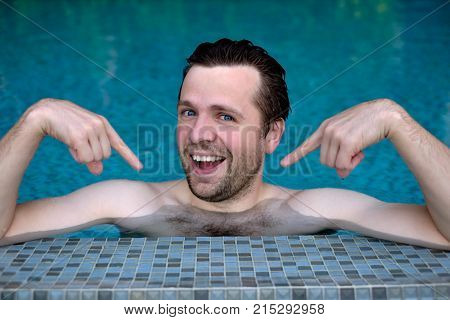 Self-satisfied and proud caucasian young man looks forward showing with index fingers on himself. He is swimming in pool during vacation
