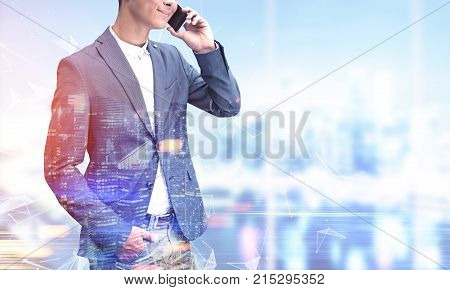 Portrait of a young unrecognizable businessman in a suit talking on the phone and smiling. He is standing against a blurred city background. Toned image mock up