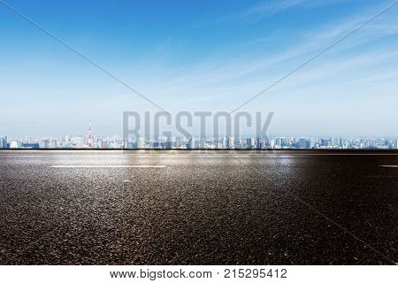 empty asphalt road and cityscape of tokyo in blue cloud sky