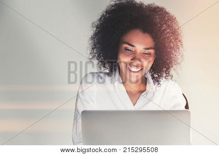 Portrait of a smiling beautiful African American businesswoman looking at her laptop screen. Toned image