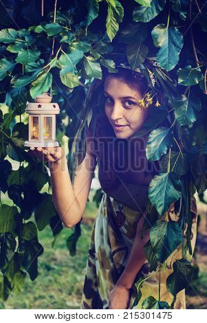 Portrait of mischievous fairy who peeps out of green foliage holding the lantern with a burning candle in her hands. Magic scene in nature. Toned image. poster