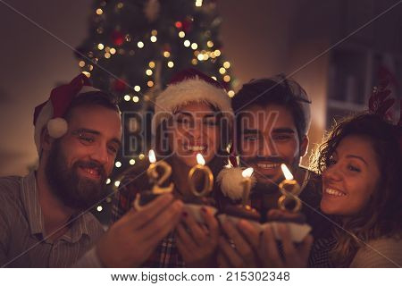 Group of young friends sitting next to a Christmas tree wearing Santa's hats holding cupcakes with 2018 candles on them. Focus on the guy on the left