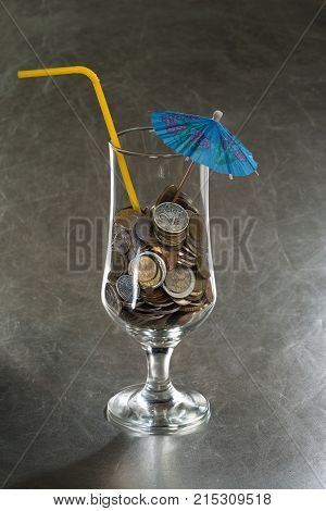 A pile of coins in a cocktail glass with an umbrella and a straw