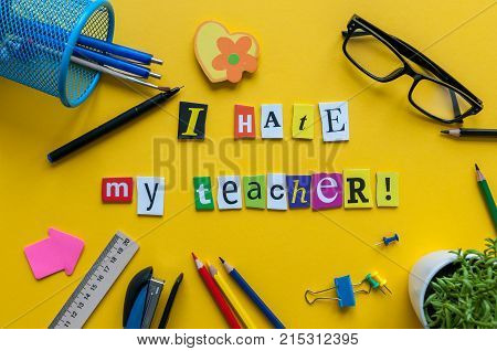 i hate my Teacher - text made with carved letters on yellow desk with office or school supplies on pupil table.