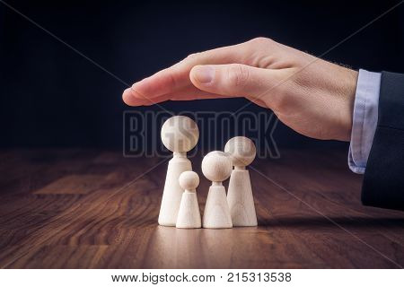Family life insurance services and supporting families concepts. Businessman with protective gesture and wooden figurines representing young insured family.