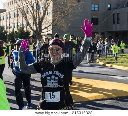 West Islip New York USA - 24 November 2017: Runners wave to the camera at the start of the Run Your Turkey Off 4K race the day after thanksgiving.