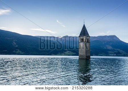 Church under water drowned village mountains landscape and peaks in background. Reschensee Lake Reschen Lago di Resia. Italy Europe Südtirol South Tyrol Upper Adige Alto Adige