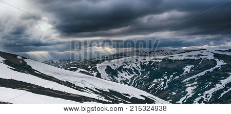 Spring mountain landscape with snow, panoramic view. Dramatic clouds lying on the horizon and sun is shining. Natural outdoor travel background in retro hipster style.