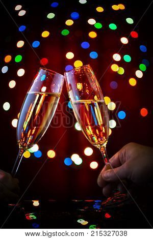 Two adjoining glasses of champagne in bokeh of garlands. The concept of celebrating the New Year and Christmas.