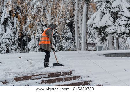 Woman with a shovel in an orange waistcoat cleans snow on the street