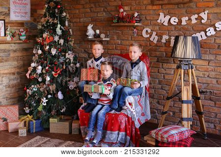 Young children boys cowed by boxes with New Years surprises, waiting to see cherished gift. Three children mens European looks dressed in warm sweaters and blue jeans  socks, smiling  laughing, sitting on large armchair  cozy room decorated  Christmas dec