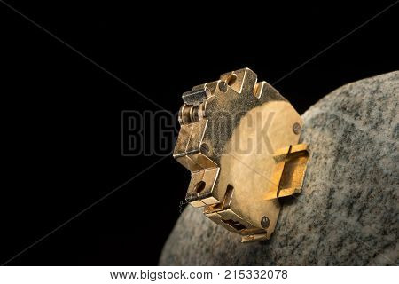 Closeup of a small golden model of a circuit breaker mounted to a polished stone poster