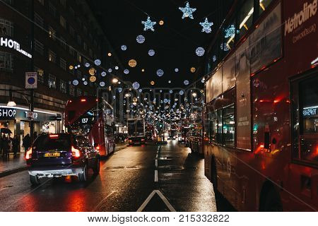 LONDON, UK - DECEMBER 20, 2016: Double Decker red buses, black cabs and cars on Oxford Street decorated with Christmas Lights. Oxford Street if one of the most famous streets in London, UK.