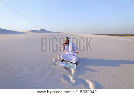 Handsome Arab businessman, talking on cell phone with companion about future construction and general business, looks at drawing and makes adjustments with ballpoint pen, sitting on white clean sand in open air desert on summer day. Swarthy Muslim with sh