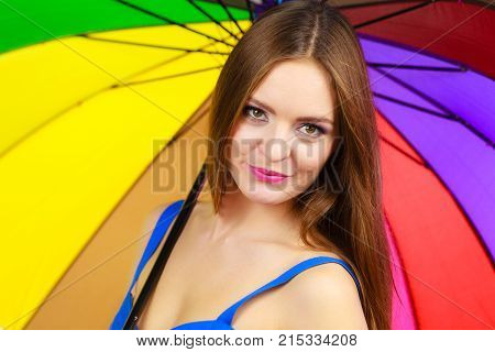 Woman fashionable summer girl standing under colorful rainbow umbrella close up. Attractive female long hair model. Forecasting and weather season concept