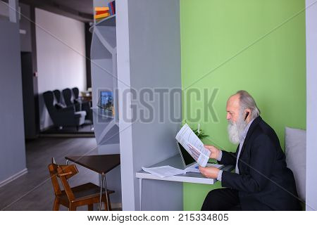 Grandpa working on pension communicates with potential business partners and negotiates bluetooth headset, reads and dictates information from documents, sits in modern office at table with laptop. Elderly man with long gray beard of European appearance d