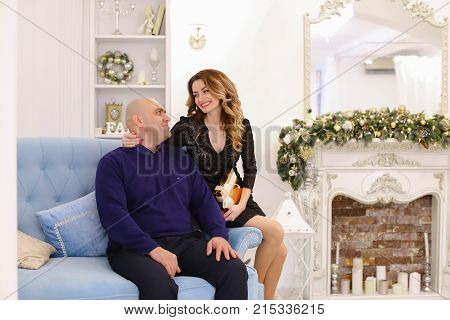Beautiful spouses, loving husband and wife smile and look at camera, pose and hug each other, sitting on soft blue couch in bright living room with fireplace decorated in festive.