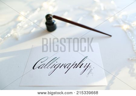 Inscription Calligraphy made in italic fine print on rectangular white sheet of paper, next to table small jar with black ink and fountain pen on light table with flickering garland. Concept of fine art and liquid paints or mascara, beautiful writing, cal