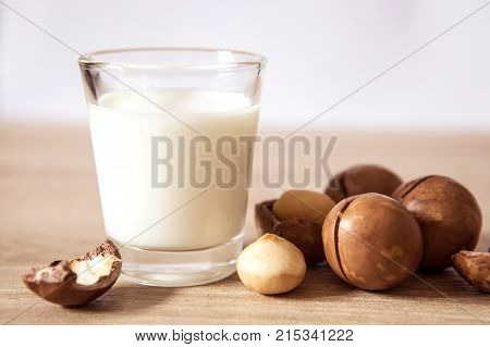 Close up a macadamia nut milk on wooden table low fat healthy drink .