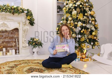 Joyful cute young woman smiling and posing with gift box with bow in hands. Woman in good mood happy with upcoming New Year holidays and shows gift to camera, sitting on carpet on floor in spacious living room with New Year's high decorated pine