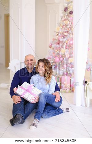 Beautiful spouses, loving husband and wife smile and look at camera, posing and hugging each other, sitting on floor in bright bedroom decorated in festive mood on background of large bed and Christmas tree.