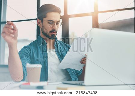Serious Young Male Enterpreneur Checks Documentation Of Month Costs, Sits In Front Of Opened Laptop,
